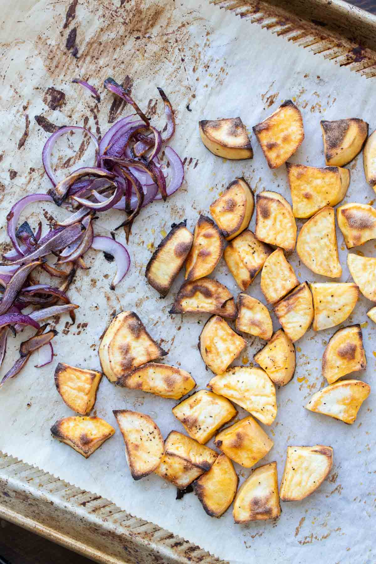 Roasted sweet potato and red onion on a piece of parchment paper