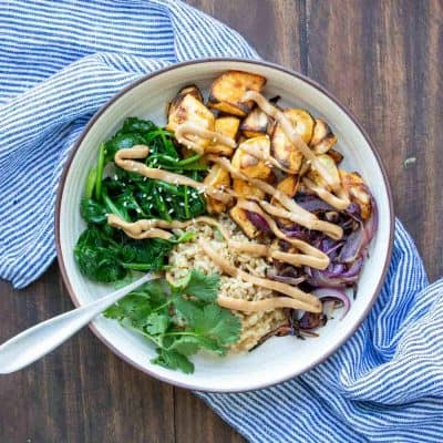 Buddha bowl with spinach, potatoes, rice and onion drizzled with sauce