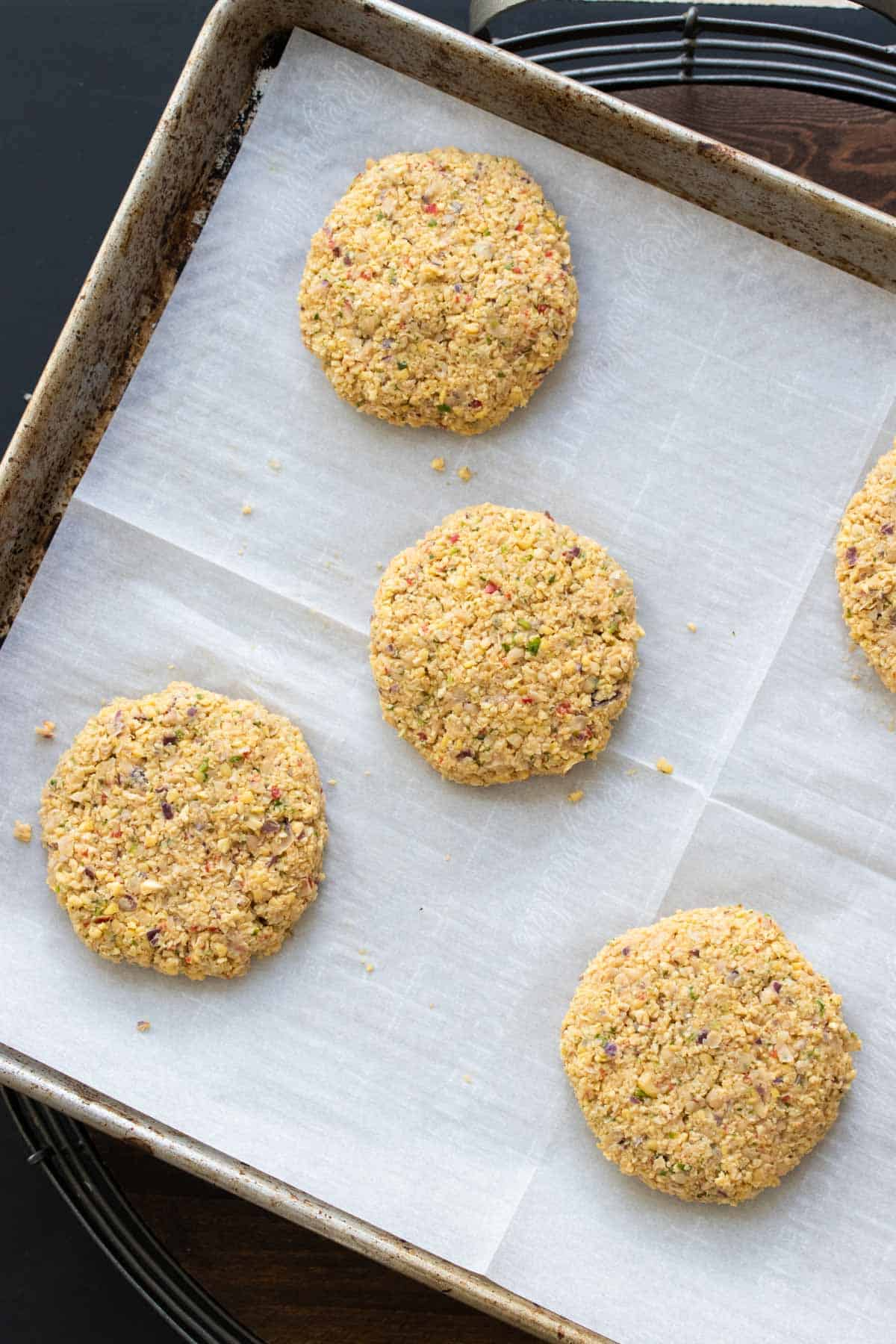 Uncooked falafel burger patties on a parchment lined baking sheet