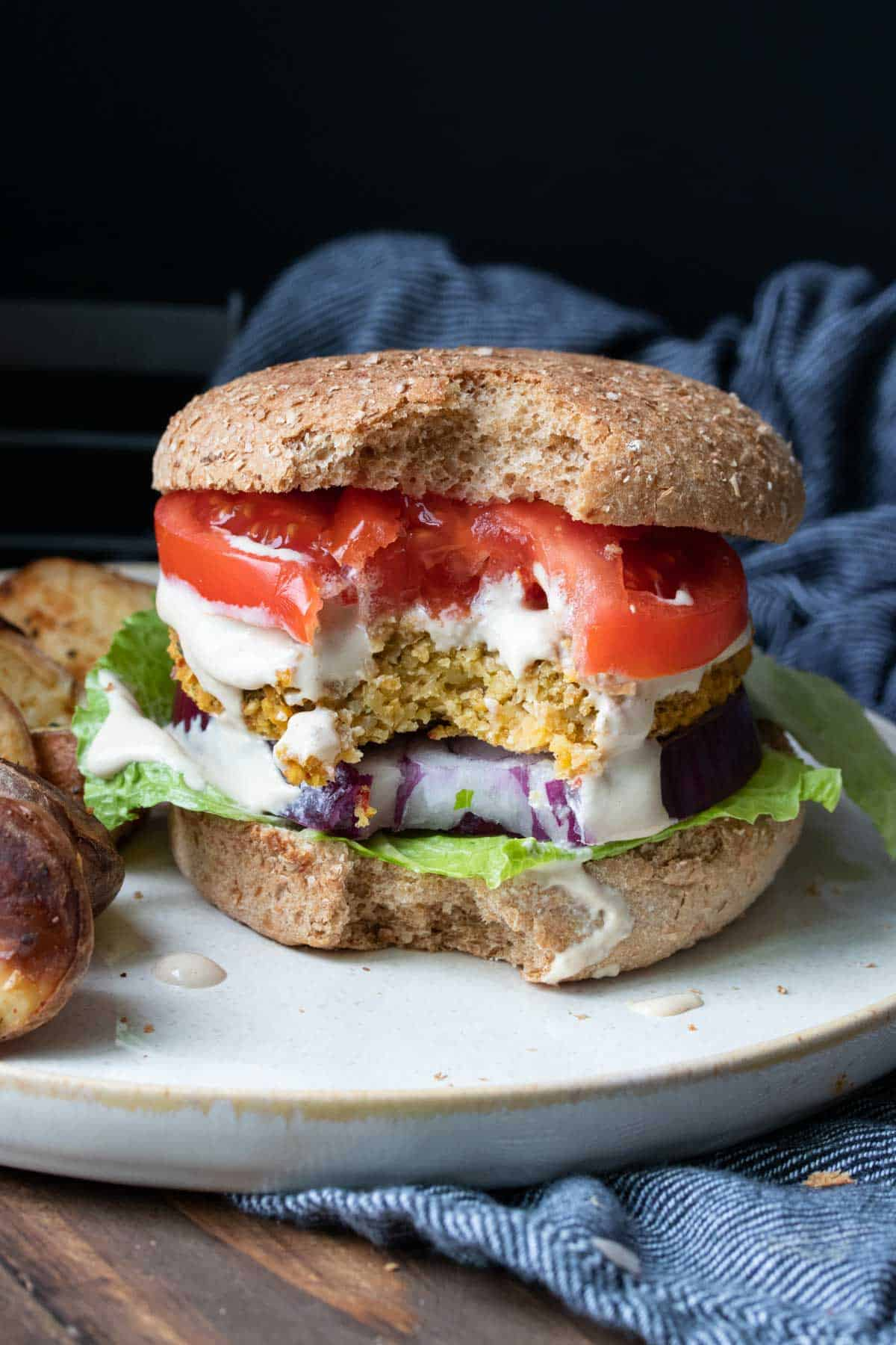 Falafel burger with lettuce, tomato and red onion and a bite out of the front
