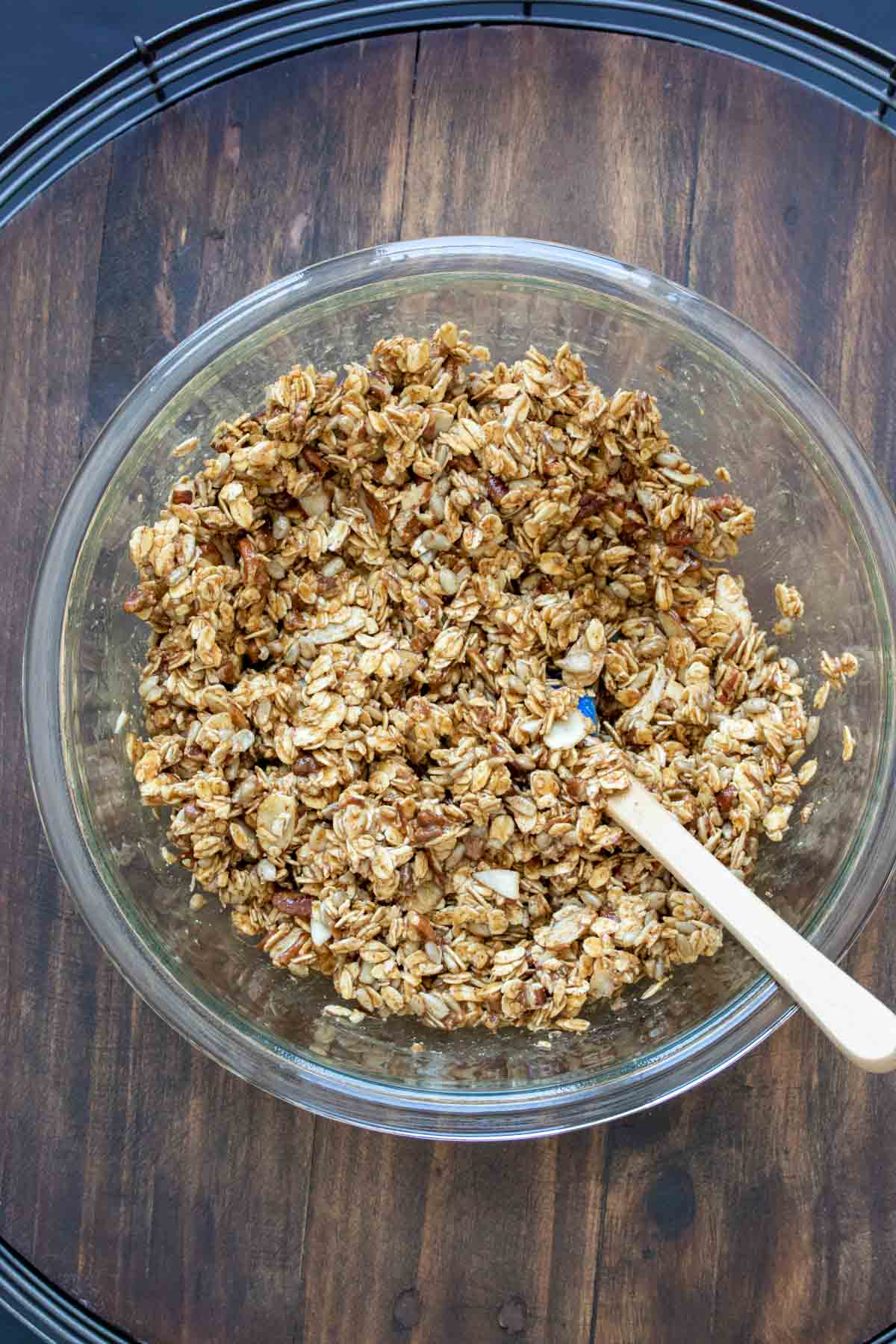 Spatula mixing ingredients for homemade granola in a glass bowl