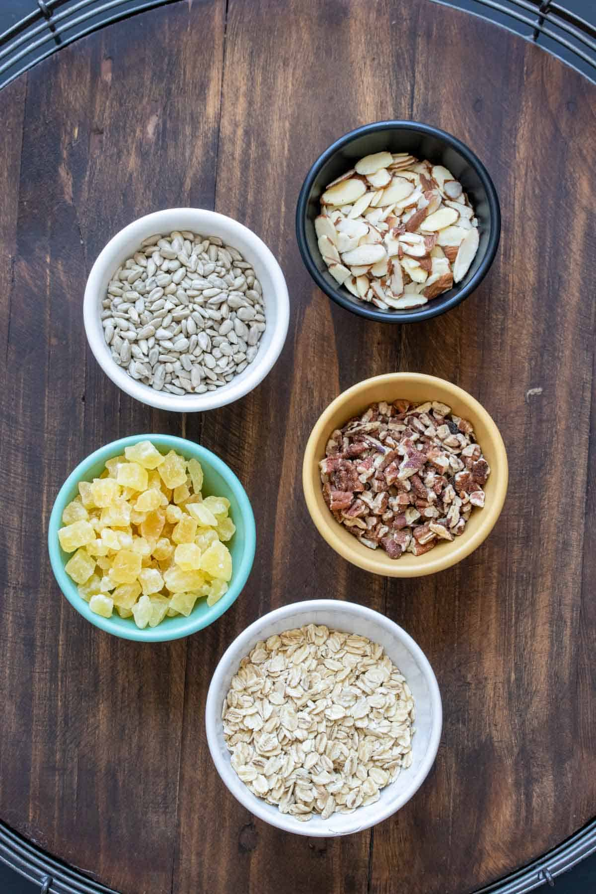 Different color bowls filled with ingredients to make homemade granola