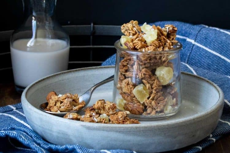 Glass jar filled with granola next to a pile of it