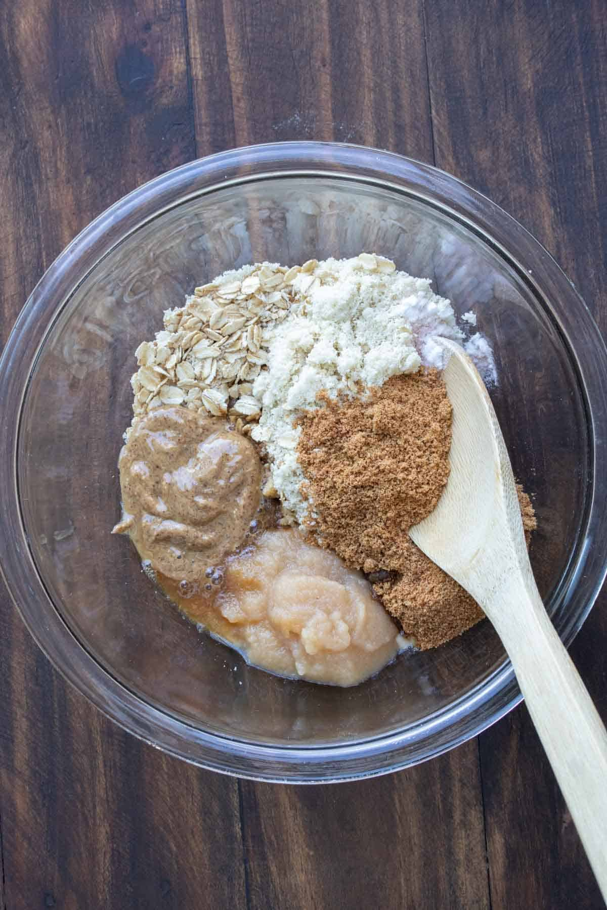 Wooden spoon mixing ingredients for oatmeal cookies in a glass bowl