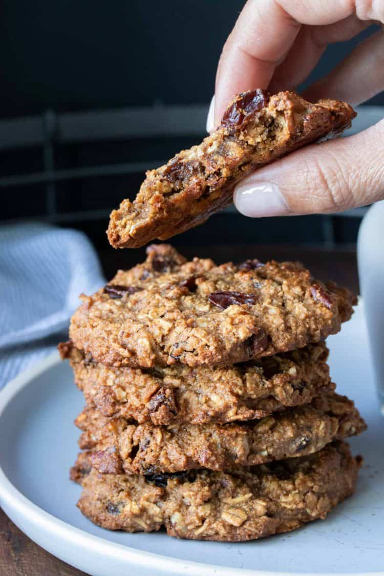 Hand holding a half eaten oatmeal raisin cookie over a stack of more