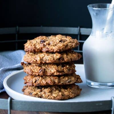 Five oatmeal raising cookies stacked on a plate next to a glass of milk