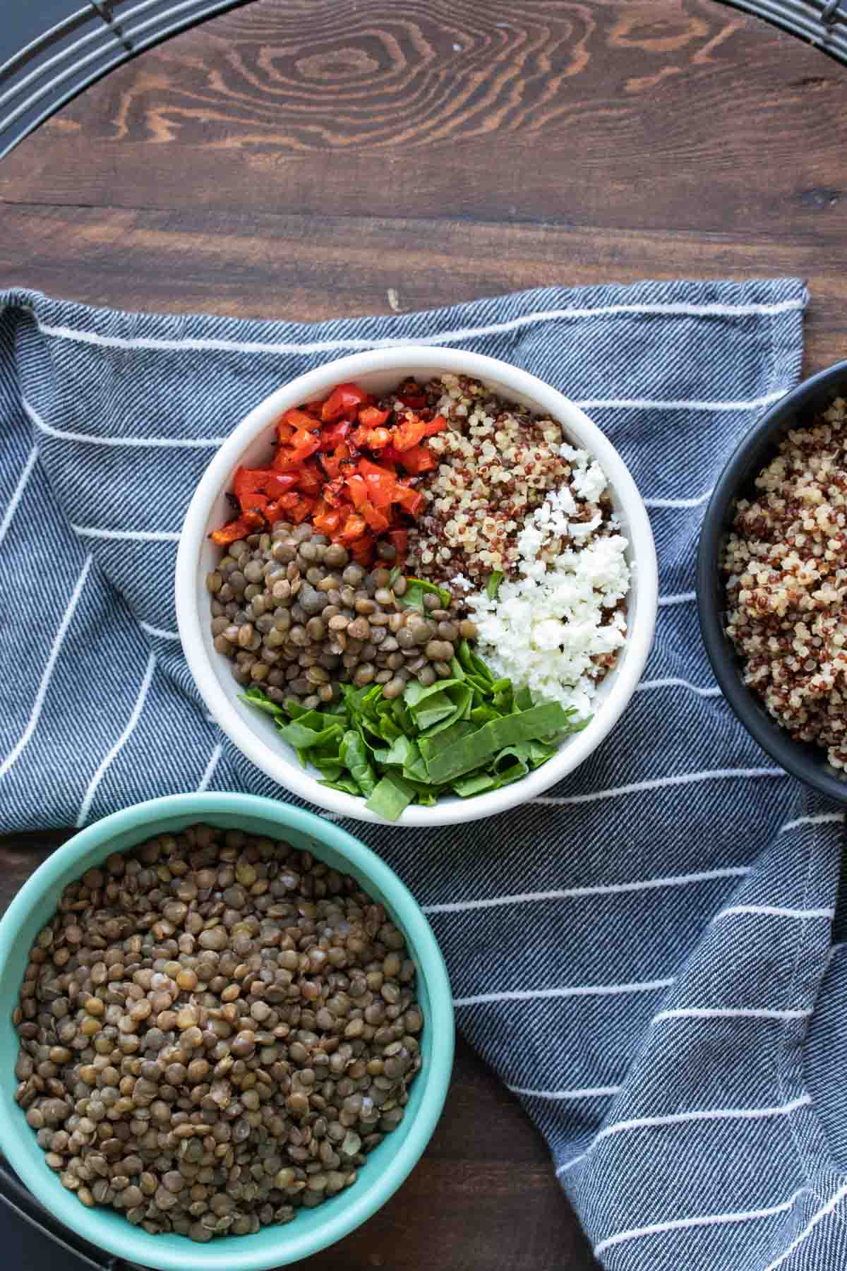Bowls of lentil quinoa salad ingredients on a blue striped towel