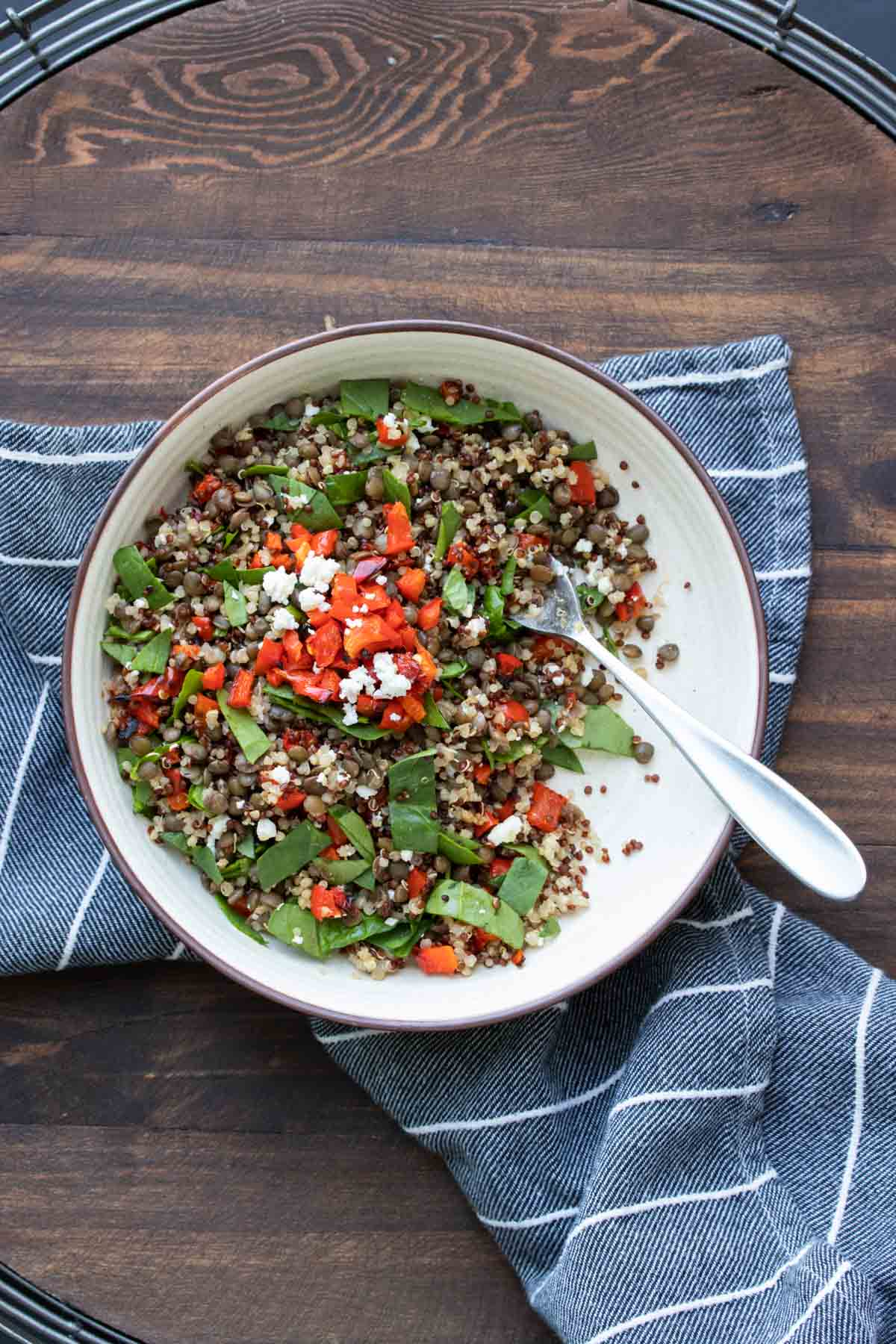 White bowl with lentil quinoa salad and red peppers