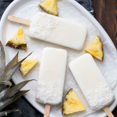 White platter of creamy looking popsicles next to pieces of pineapple