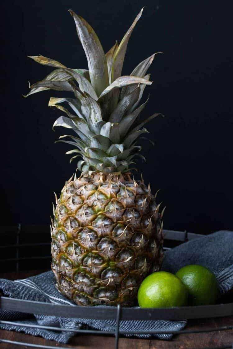 A pineapple next to 2 limes on a blue kitchen napkin