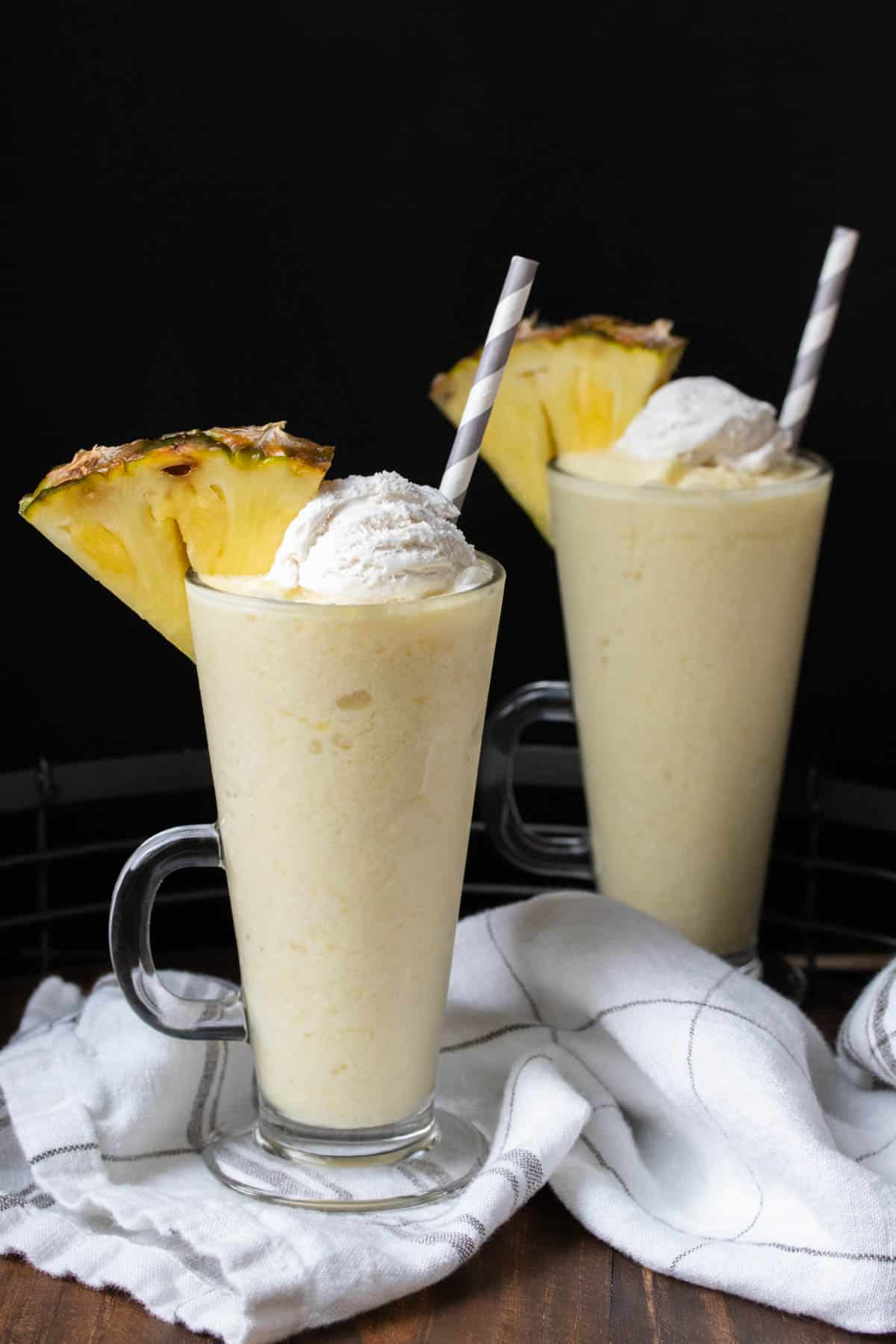 Two pina colada smoothies with whipped cream and a pineapple slice