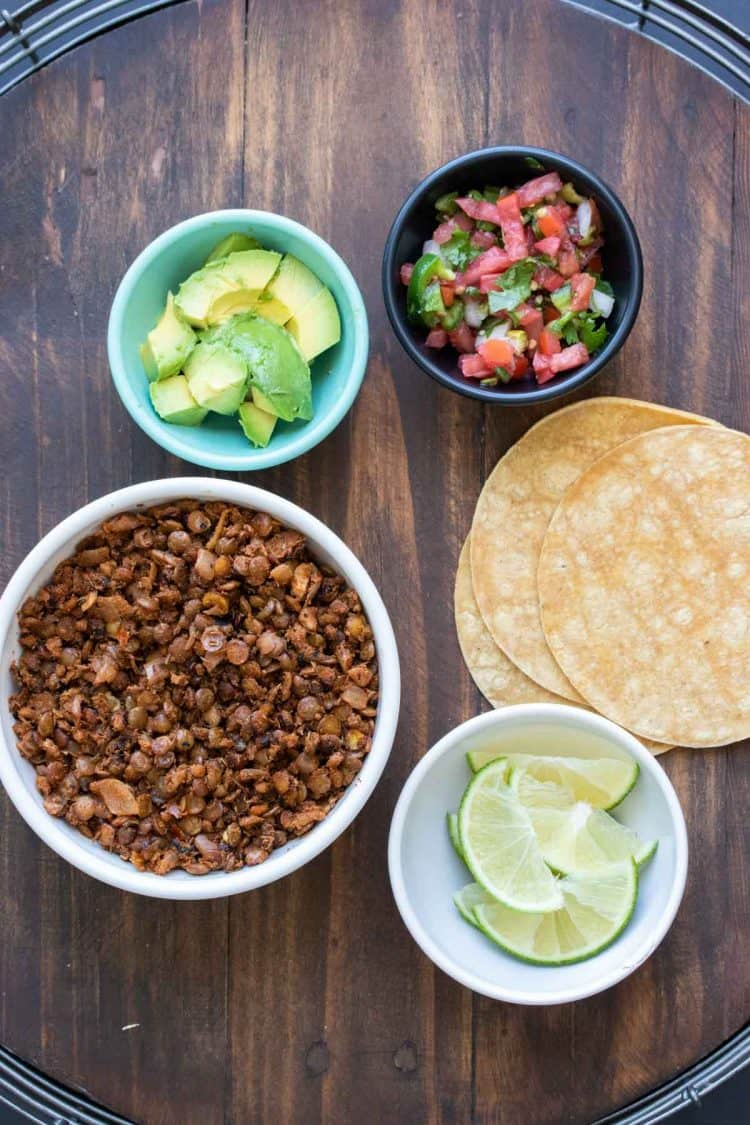 Bowls with taco ingredients on a table with corn tortillas