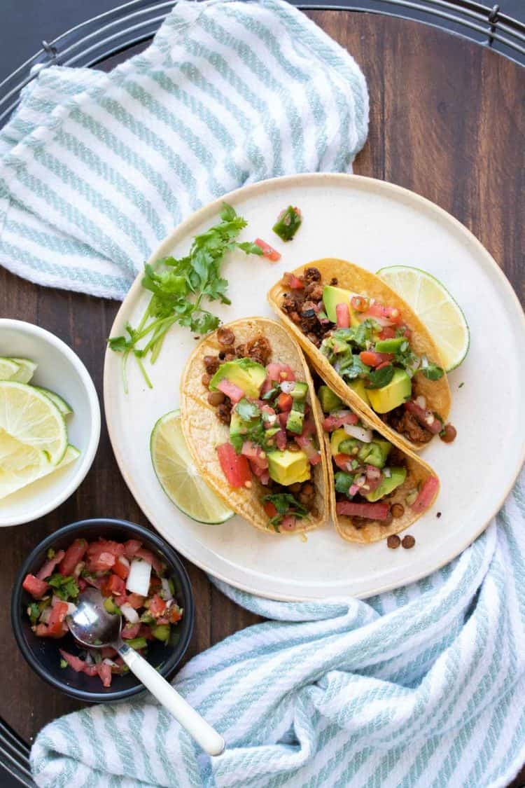 White plate with tacos filled with lentil taco meat and toppings