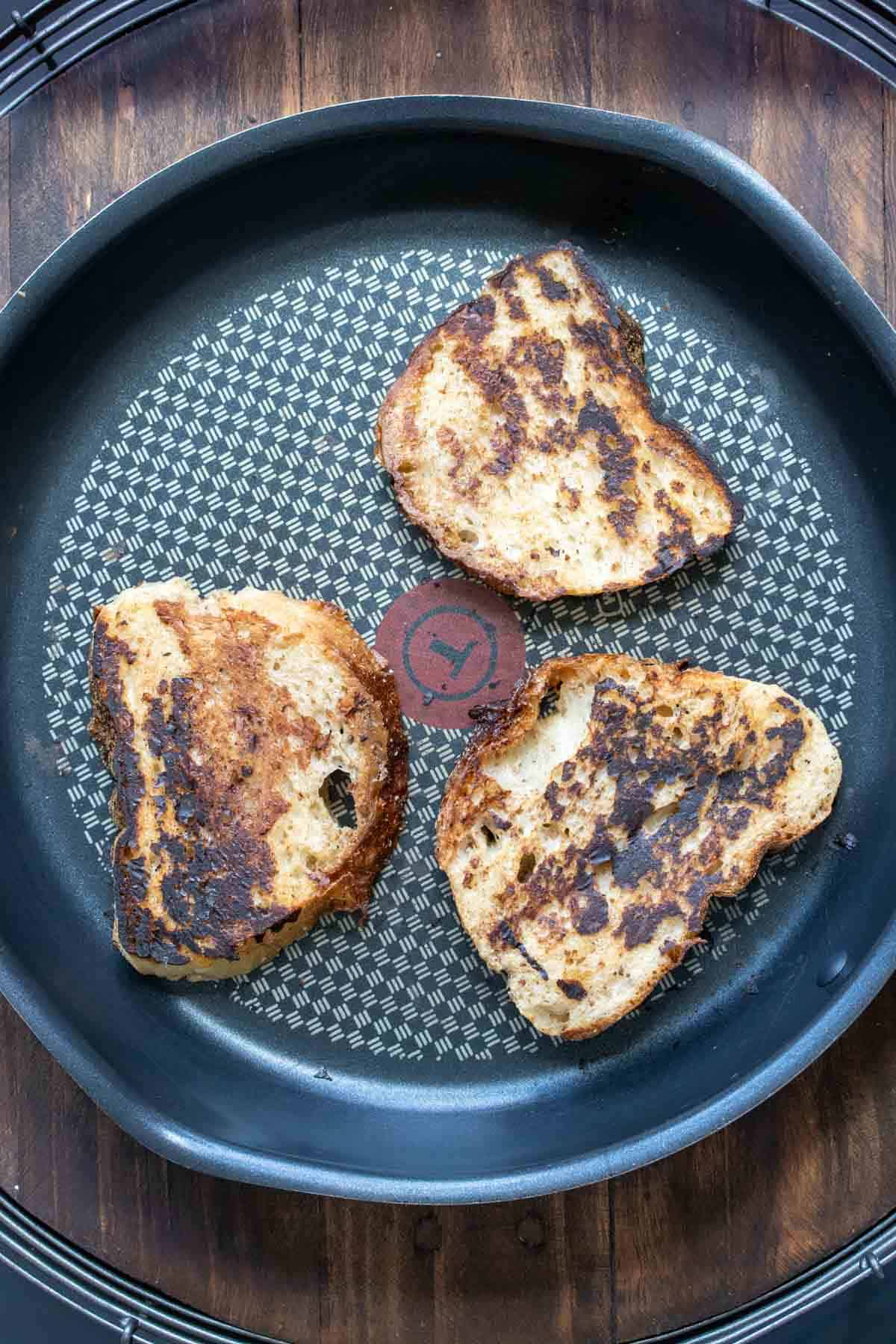 Three pieces of French toast being grilled on a pan