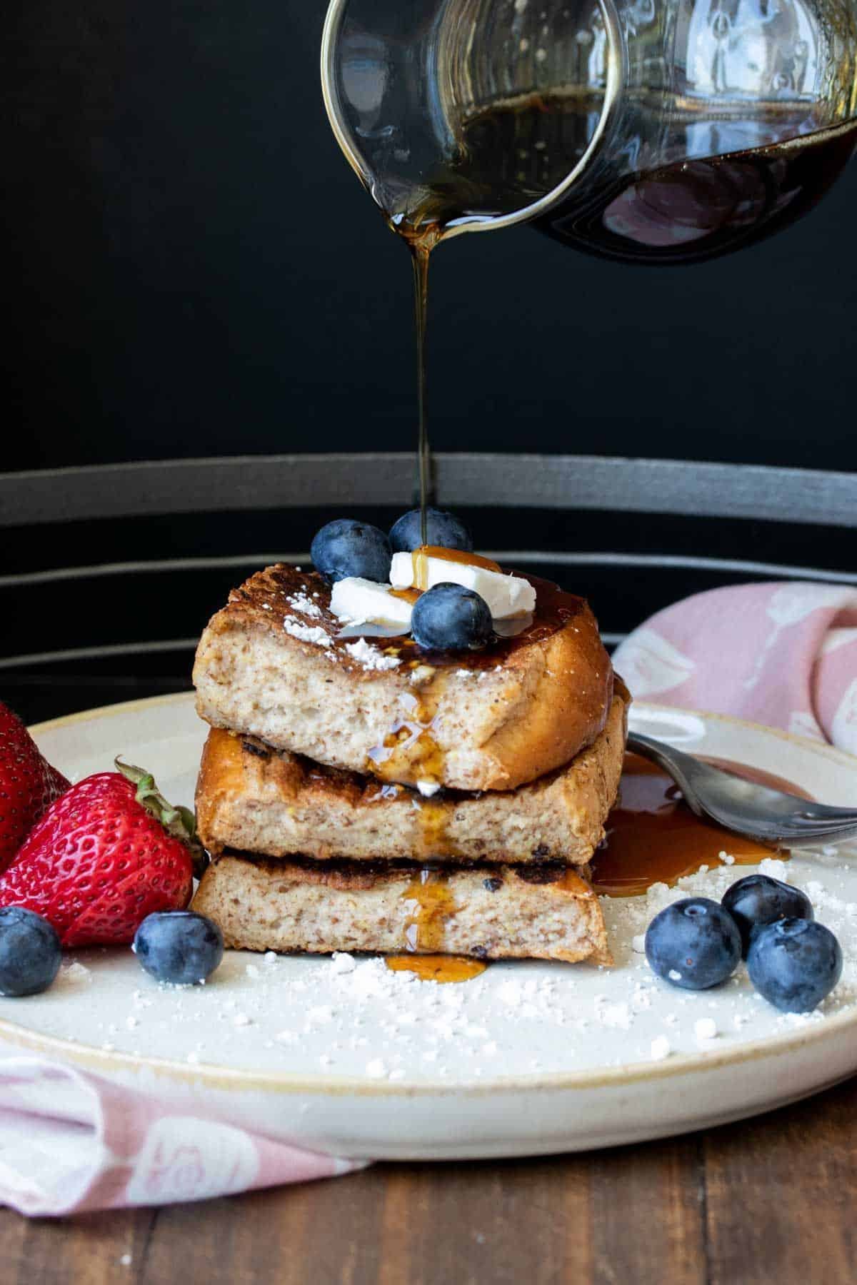 Maple syrup being poured onto a pile of French toast and berries