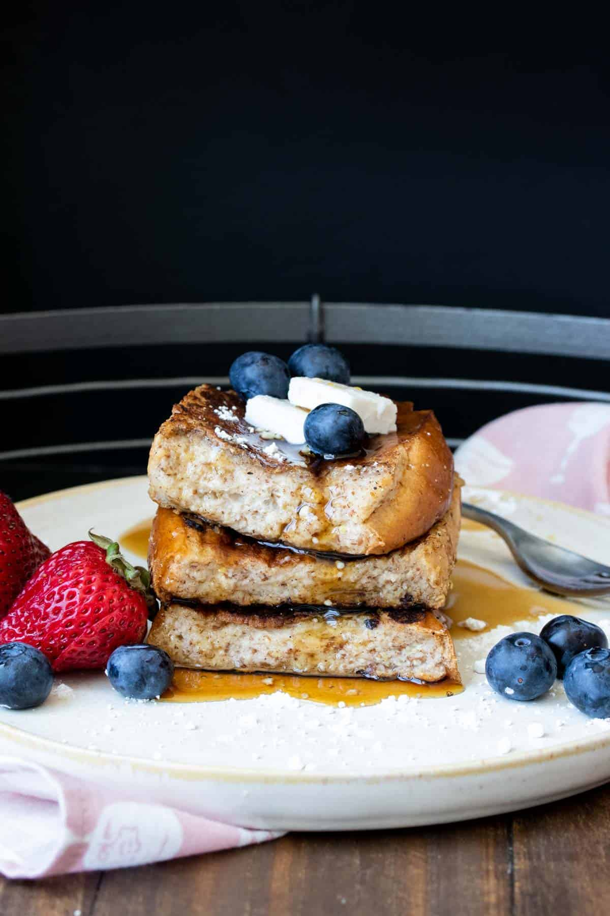 Three pieces of French toast topped with butter and berries piled up