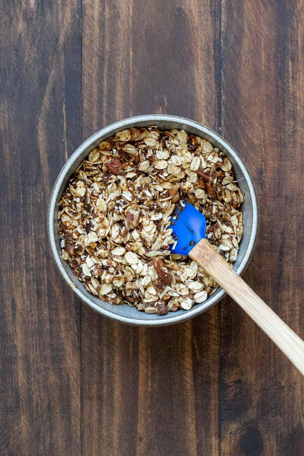 Spatula mixing oats, nuts and sugar in a grey bowl