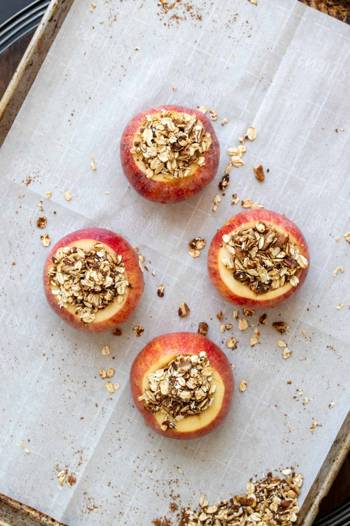 Four raw cored apples topped with an oat filling