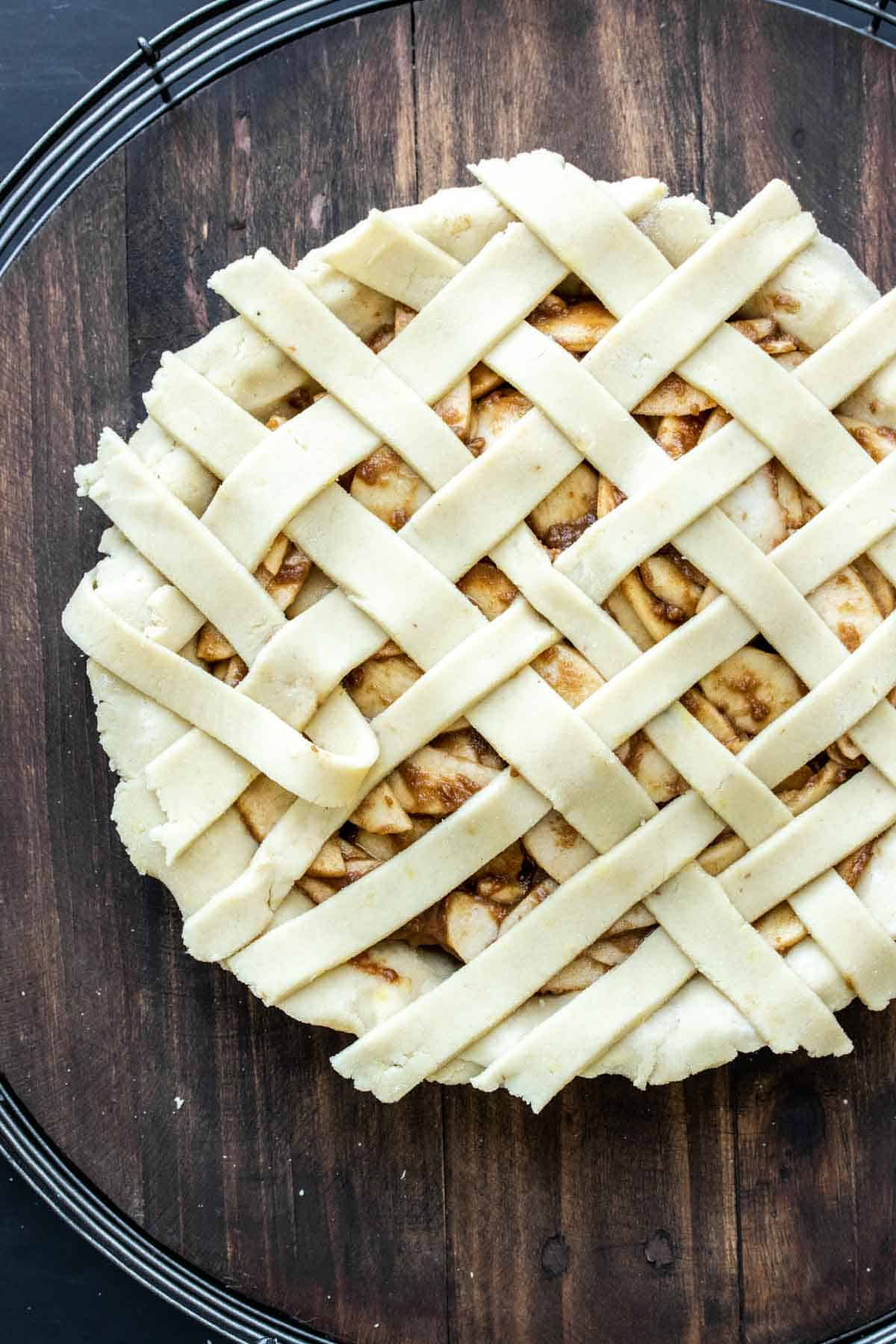 A raw apple pie with strips of pie dough being woven