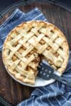 A spatula taking out a piece of apple pie from a pie dish