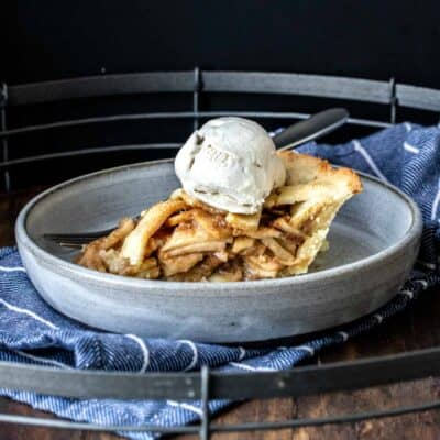 A piece of apple pie topped with ice cream on a grey plate