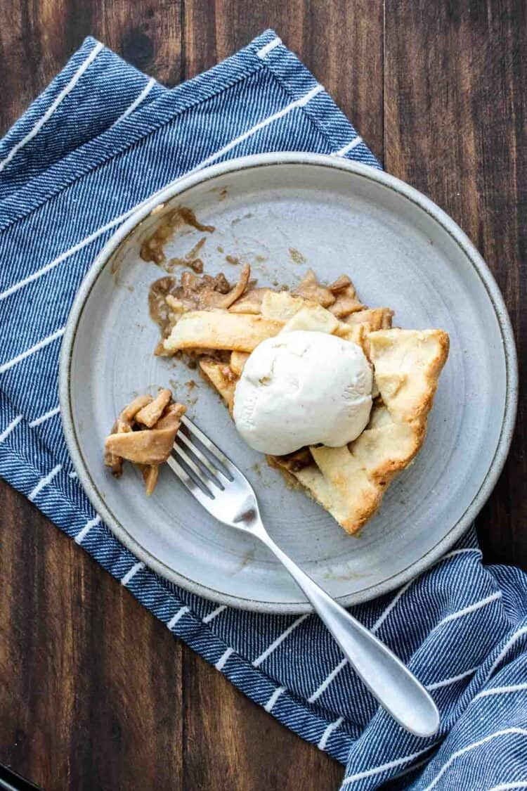 Top view of a fork eating a piece of apple pie topped with ice cream