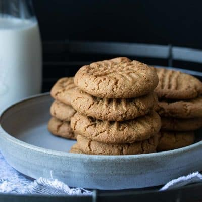 Grey plate with a pile of peanut butter cookies on it next to a glass of milk