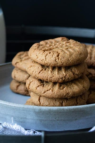 Grey plate piled with stacks of peanut butter cookies next to a glass of milk