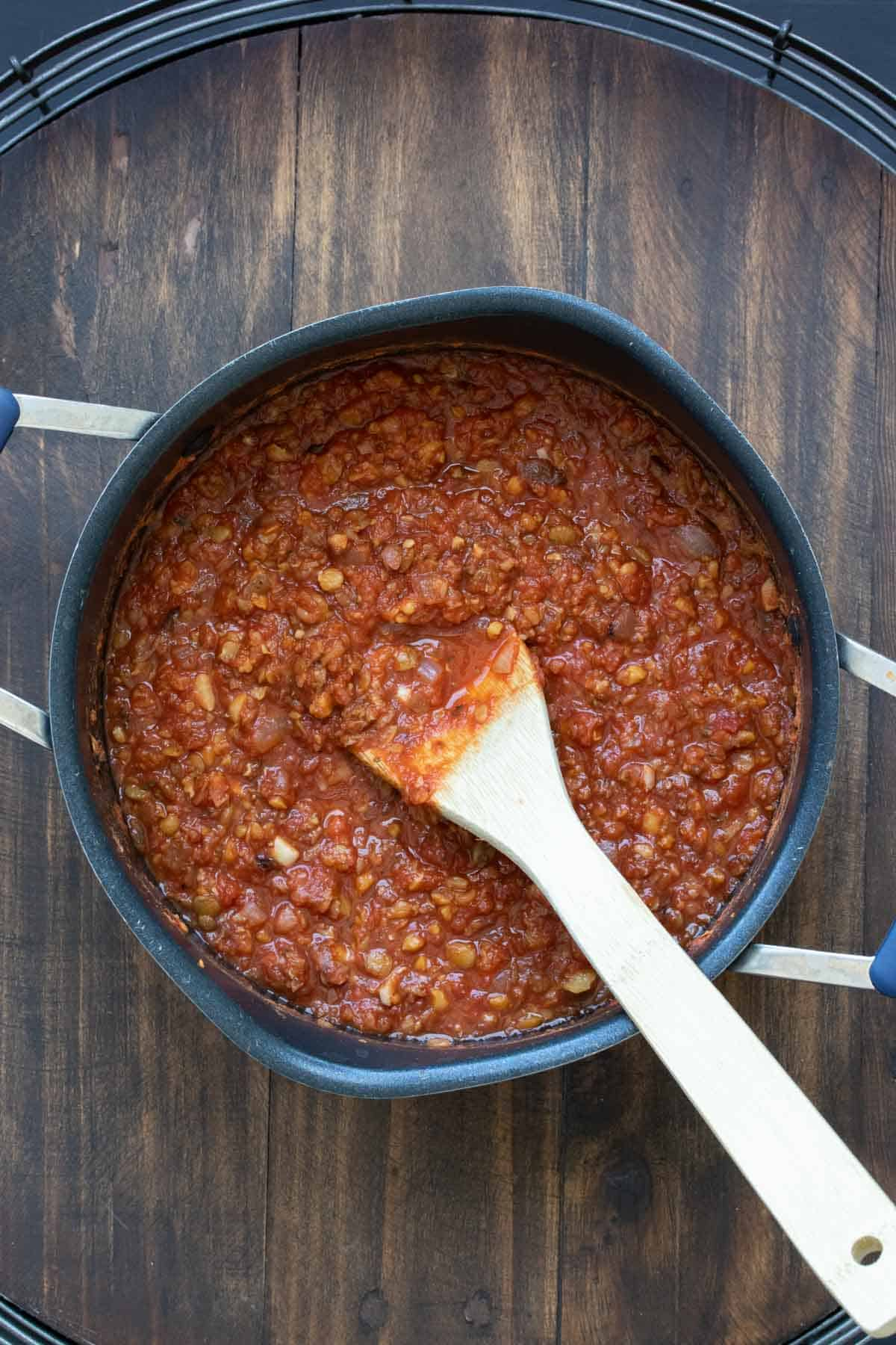 Wooden spoon mixing a bean based marinara in a pot