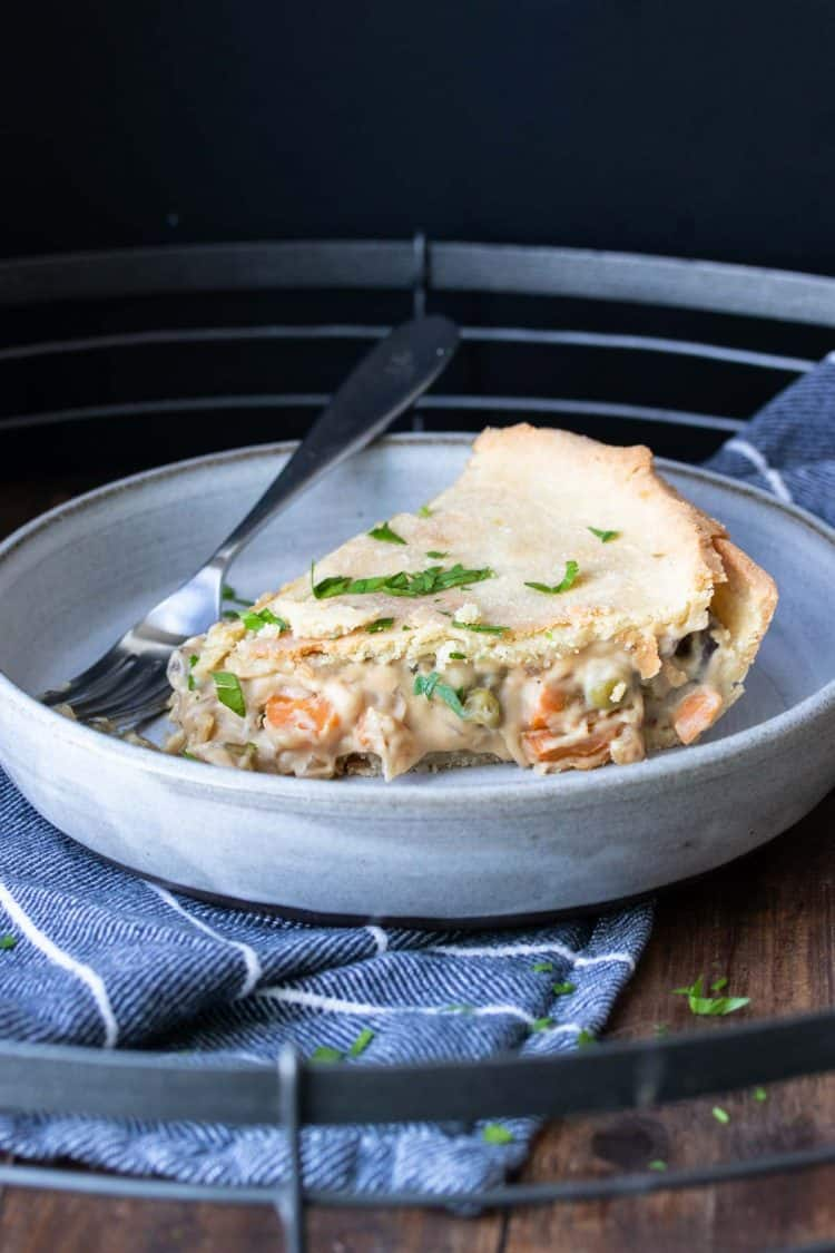 A piece of veggie pot pie on a plate with a fork next to it