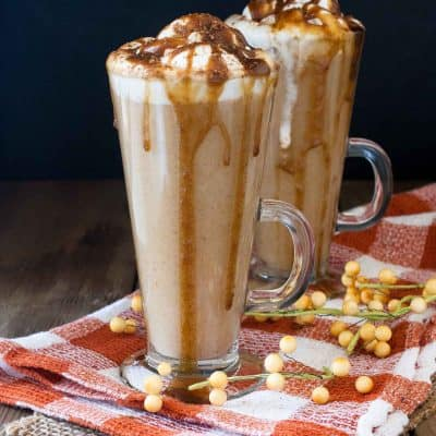 Two tall glasses on an orange checkered towel filled with a pumpkin spice latte drink