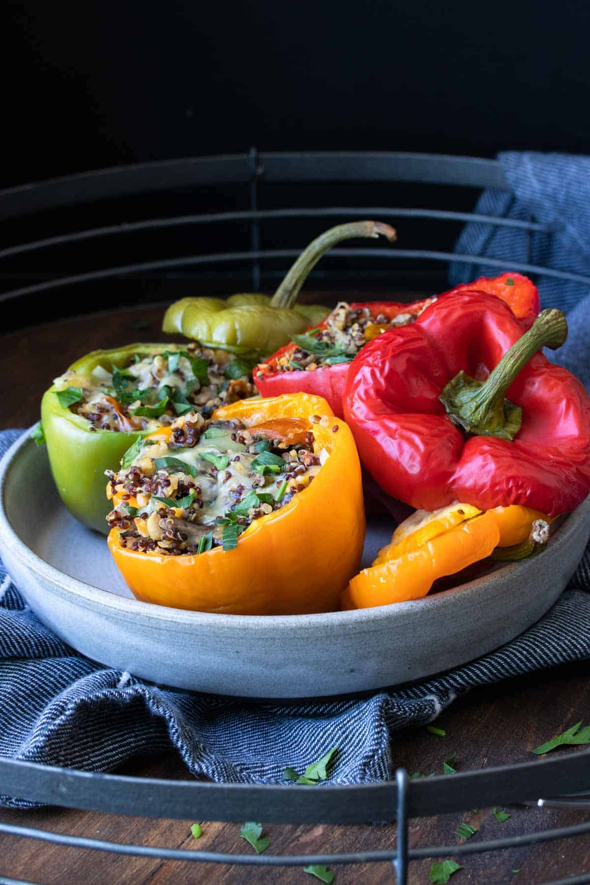 Grey plate with tri colored quinoa stuffed peppers
