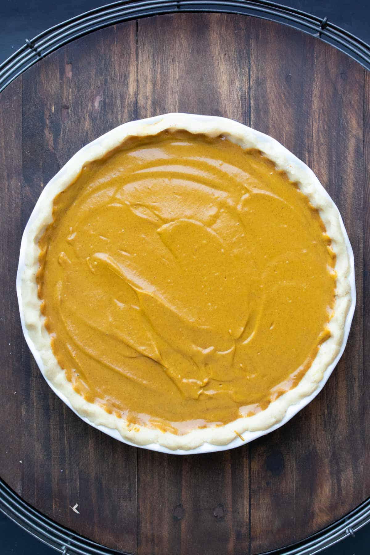 A raw pumpkin pie in a pie crust on a wooden surface