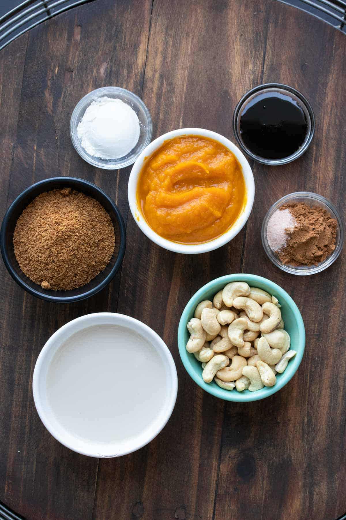 Ingredients for pumpkin pie filling in different colored bowls