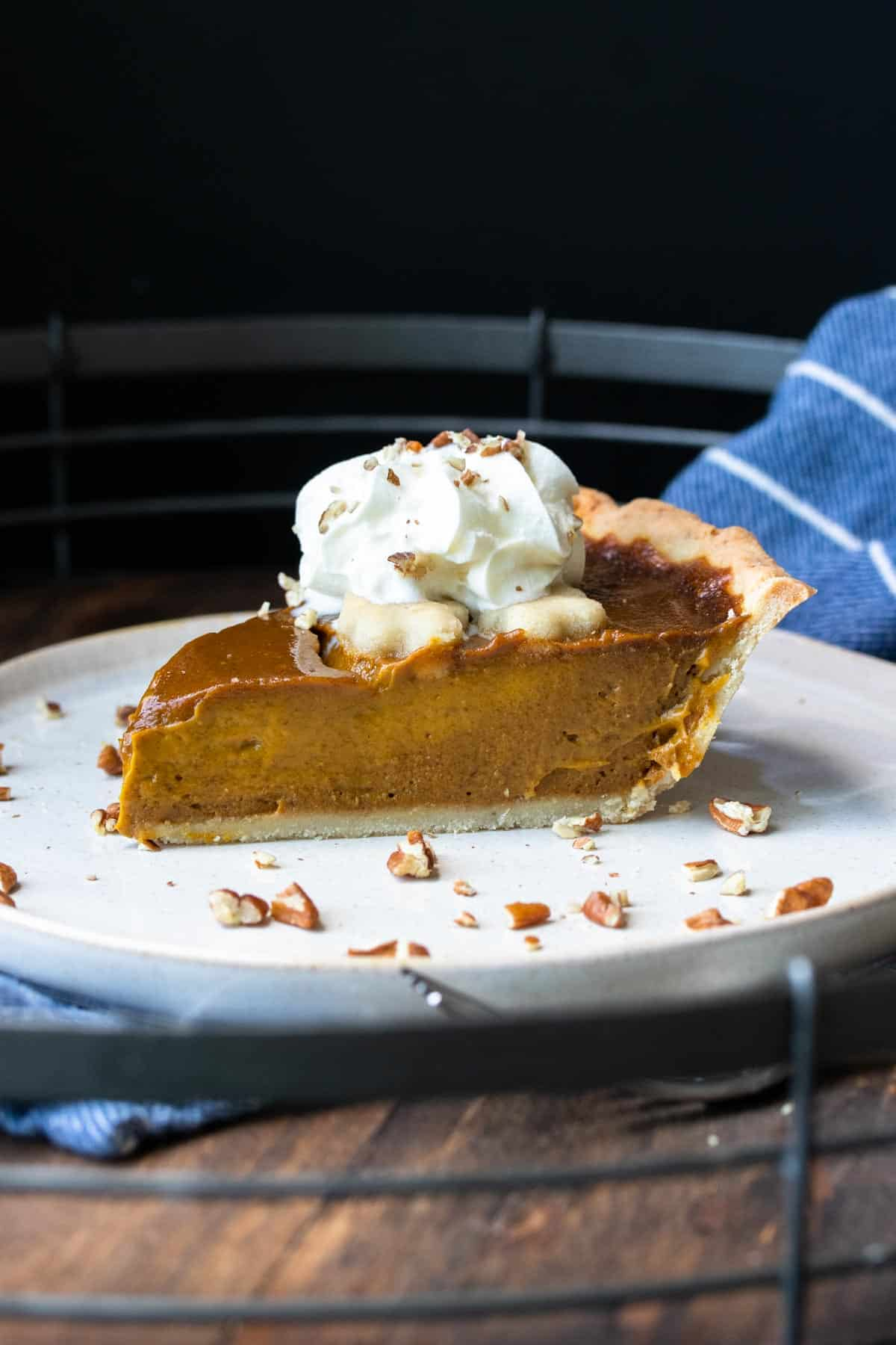 A slice of pumpkin pie on a white plate topped with whipped cream