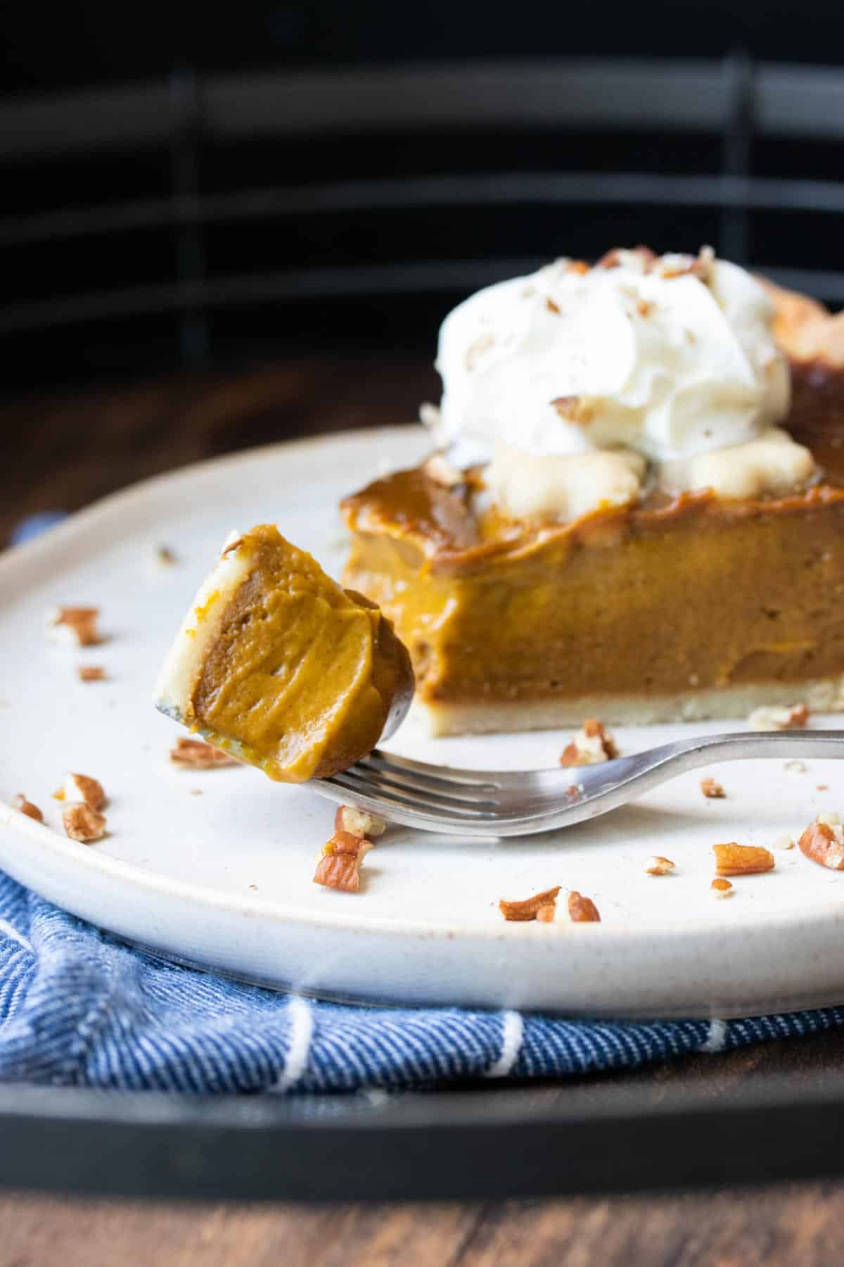 Front view of a fork with a bite of pumpkin pie on a plate