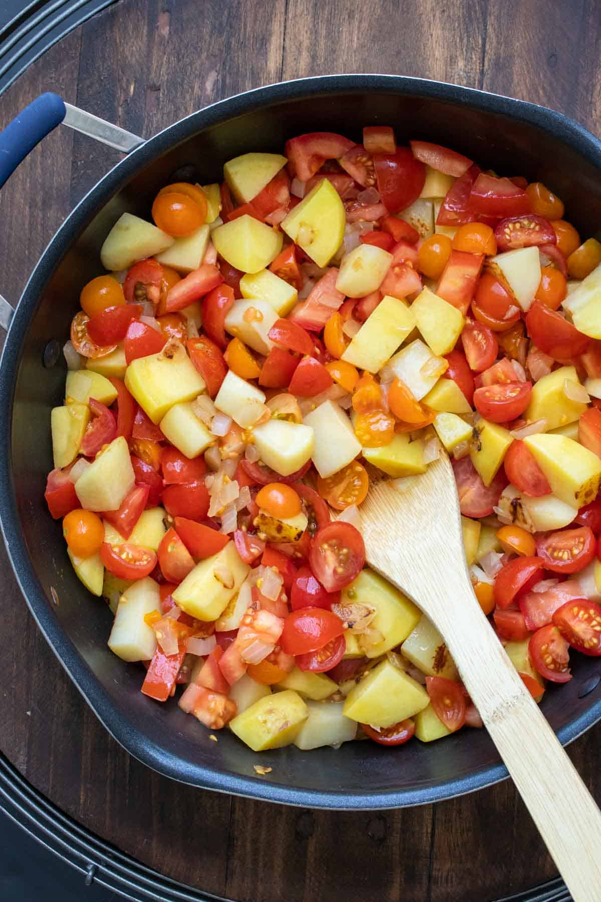 Potatoes and tomatoes being cooked in a pan