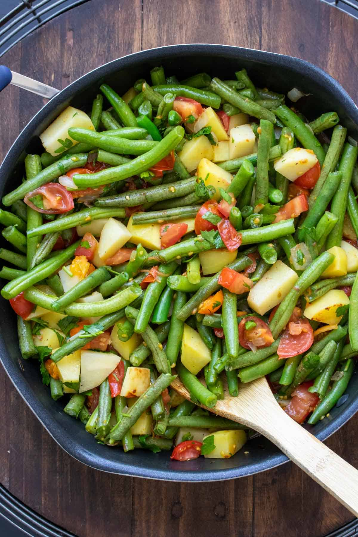 Wooden spoon stirring green beans, potatoes and tomatoes in a pan