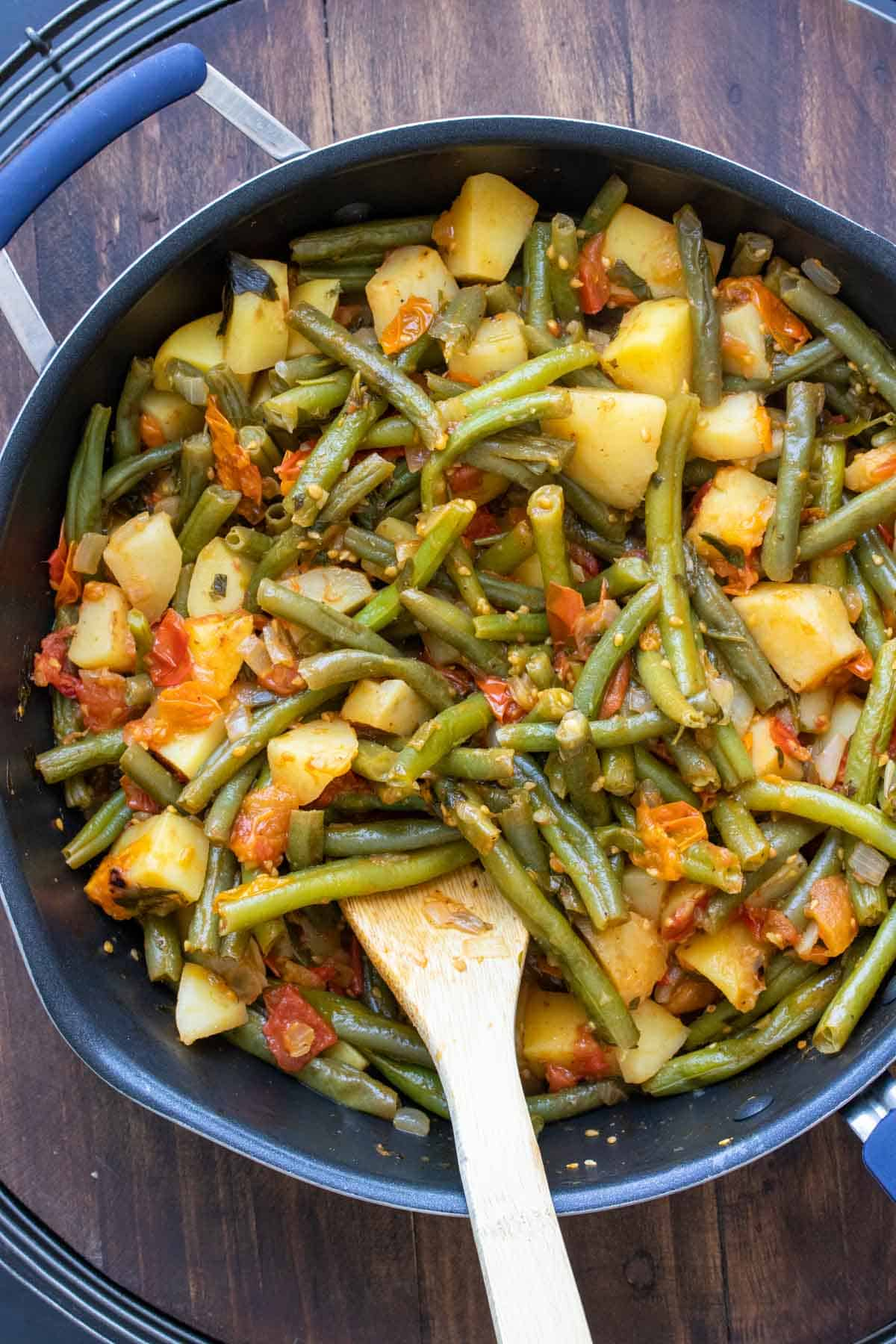 Cooked green beans with potatoes and tomatoes in a pan