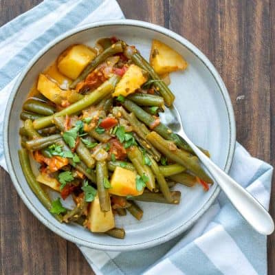 Sautéed green beans with potatoes and tomatoes on a grey plate