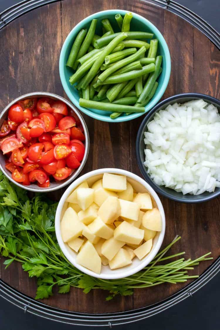 Bowls filled with veggies to make Greek green beans