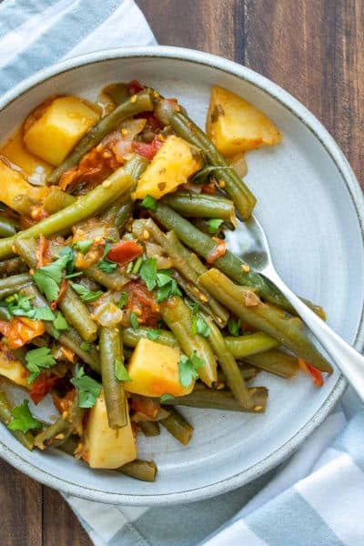 Sautéed green beans and potatoes in a tomato sauce on a grey plate