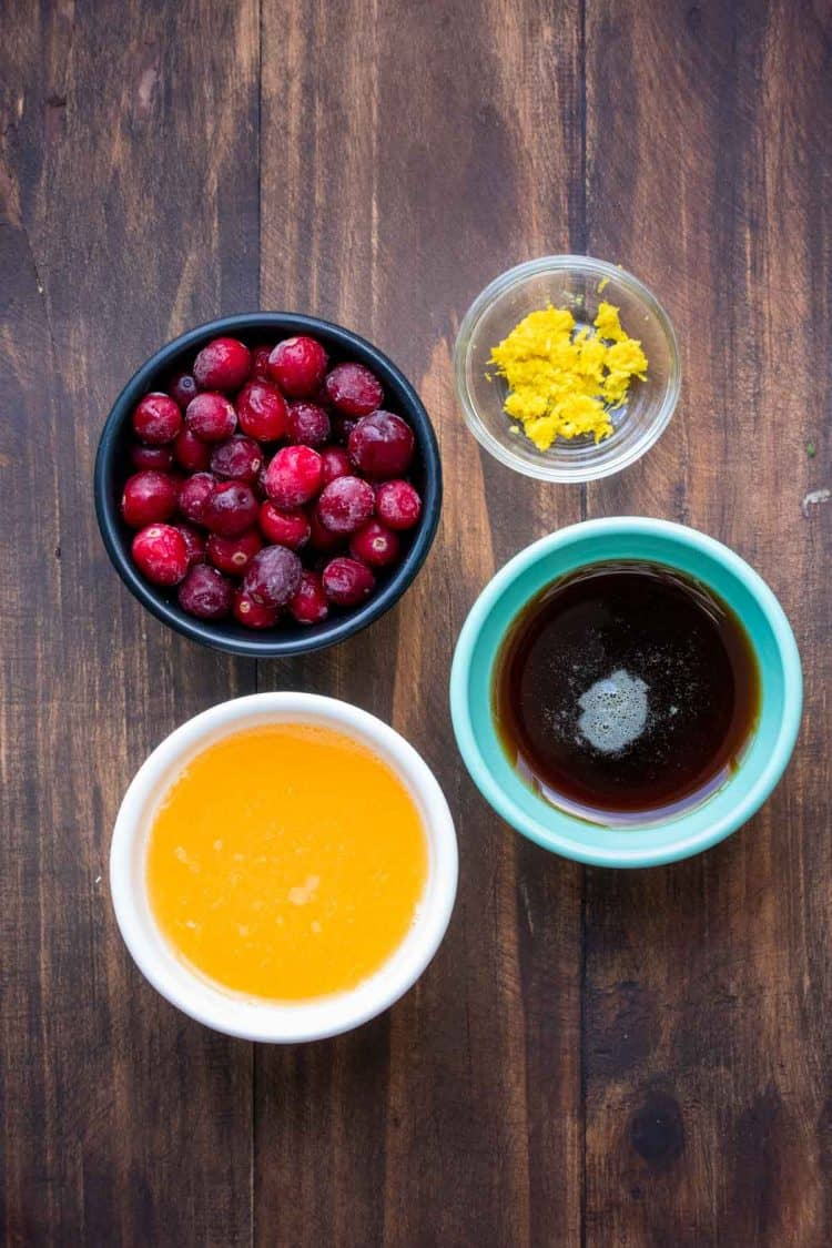 Bowls with ingredients for cranberry sauce made with orange juice