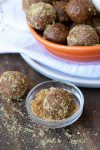 Pumpkin energy ball being rolled in crushed graham crackers in a glass bowl