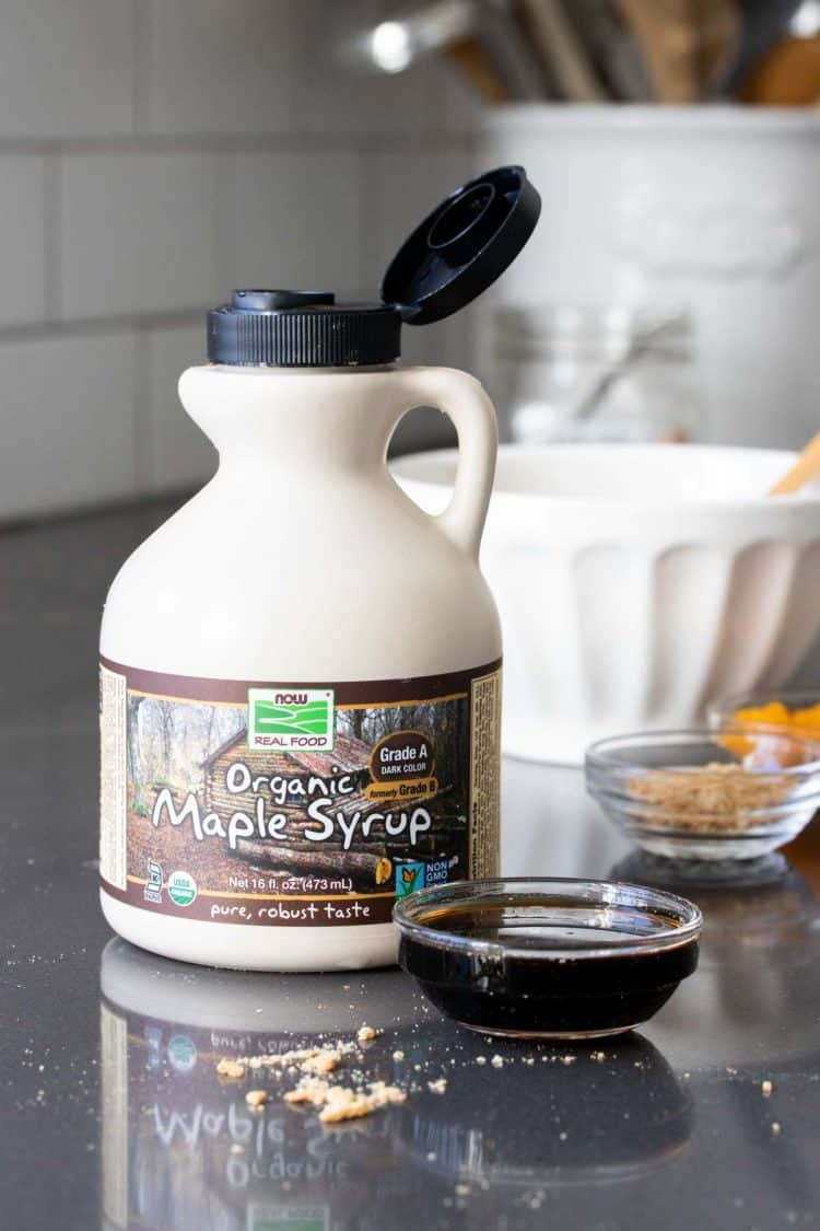 A cream colored container of maple syrup on a grey surface