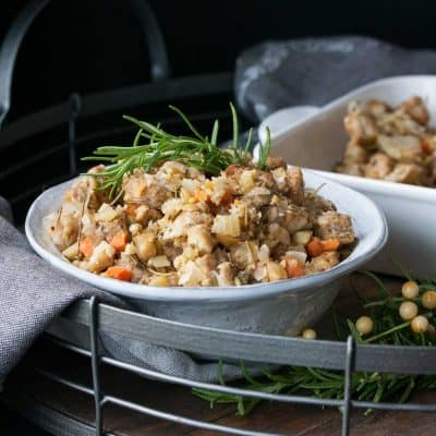 Thanksgiving stuffing with a sprig of rosemary in a white bowl on a wooden tray