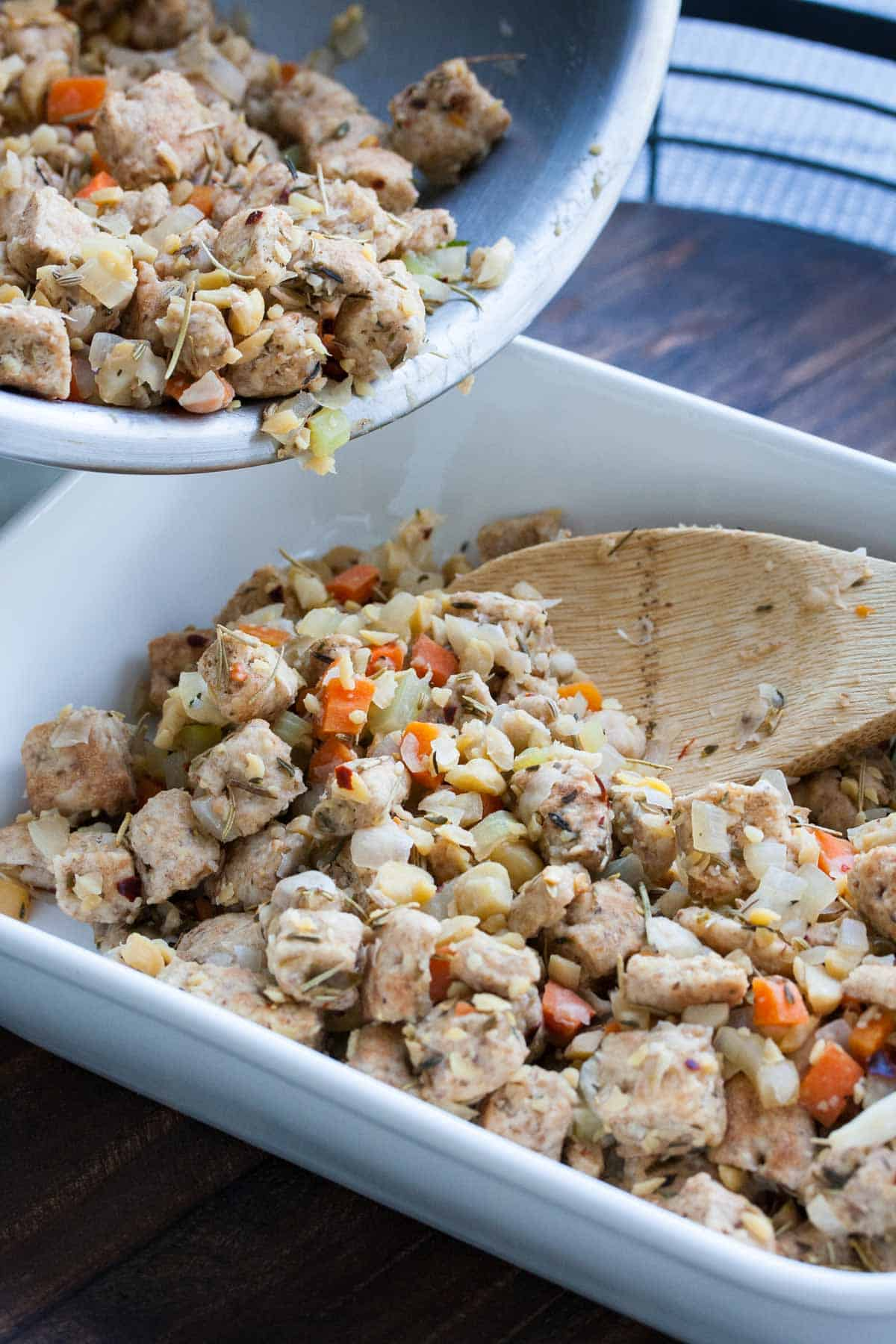Pouring stuffing from silver bowl into white baking dish with a wooden spoon