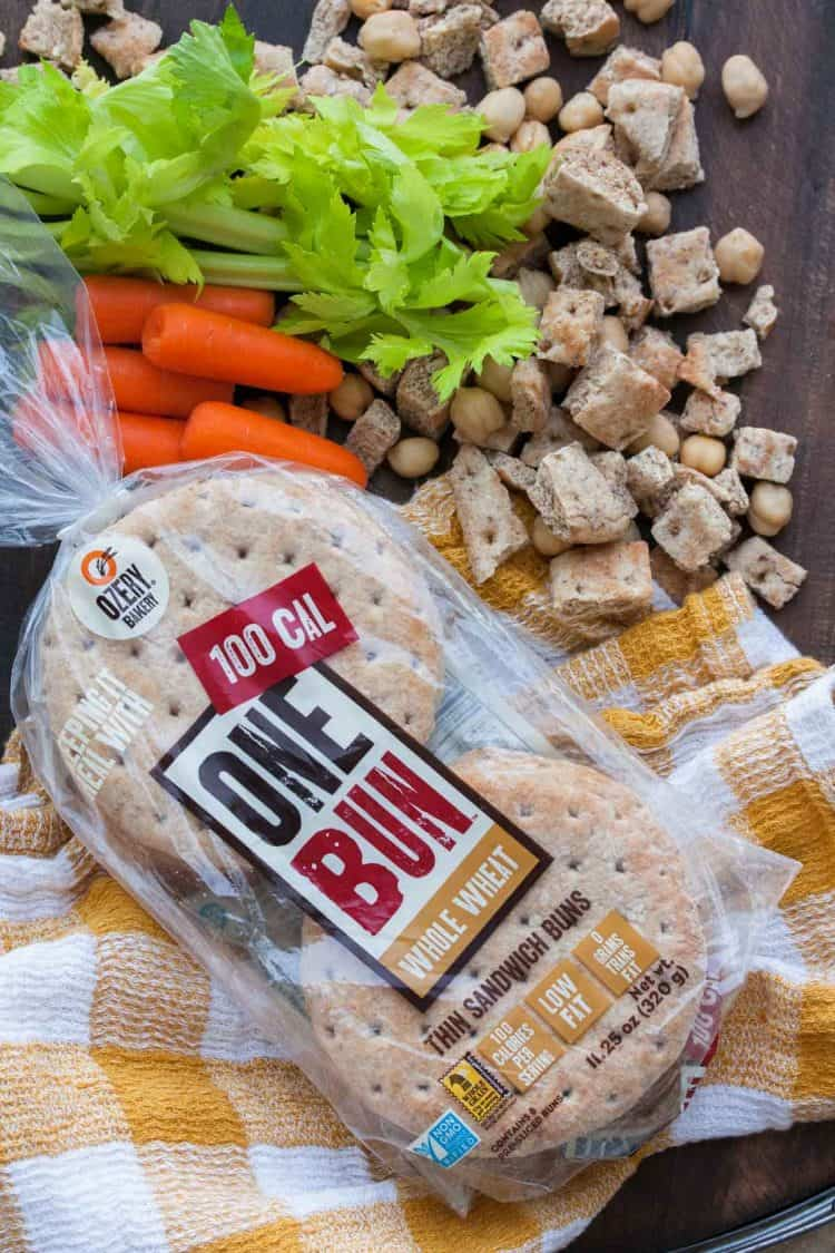 Package of bread surrounded by cubed bread pieces and chopped veggies