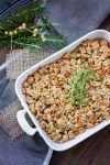 Top view of white baking dish full of stuffing sitting on a grey towel