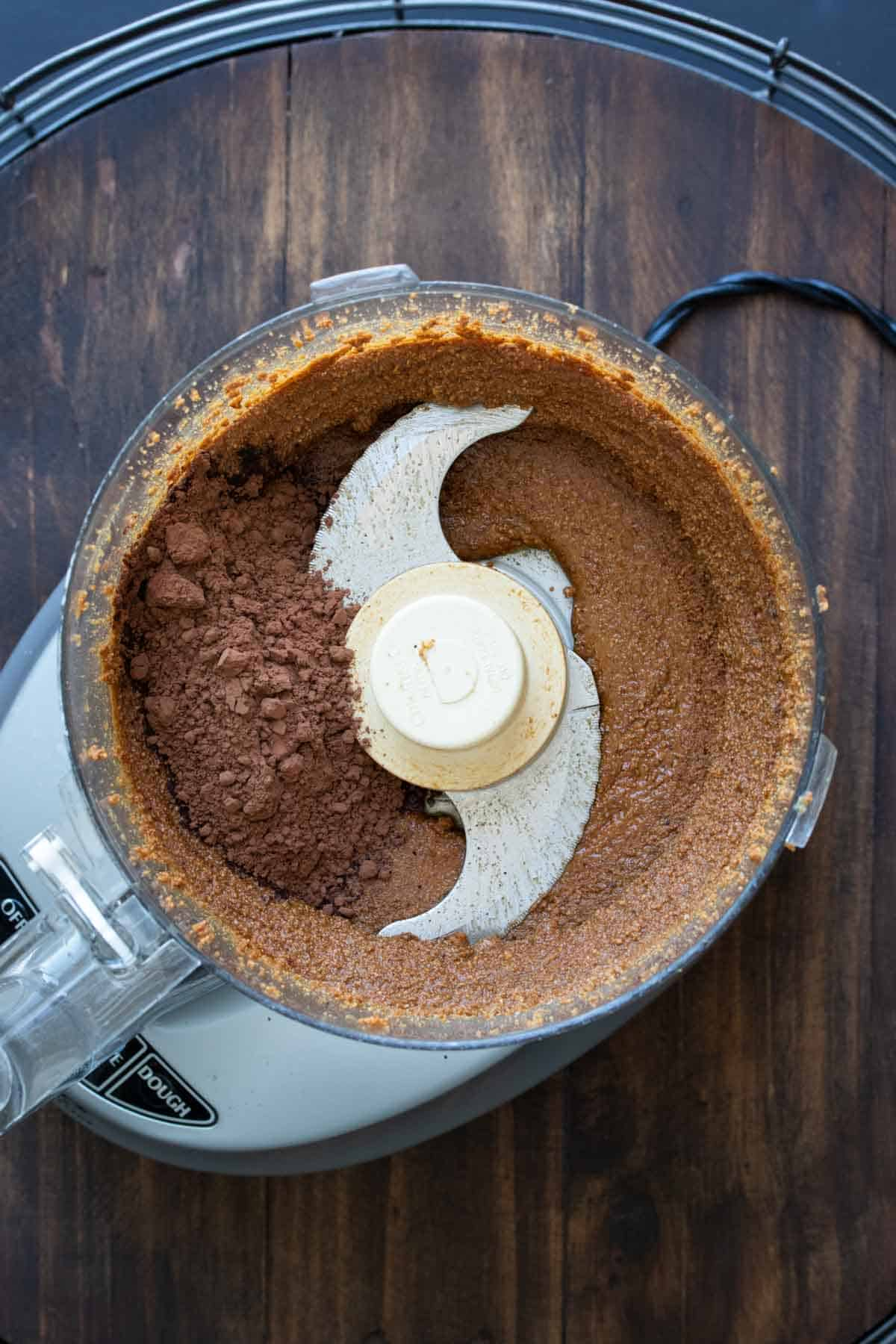 Food processor blending hazelnuts and cocoa powder